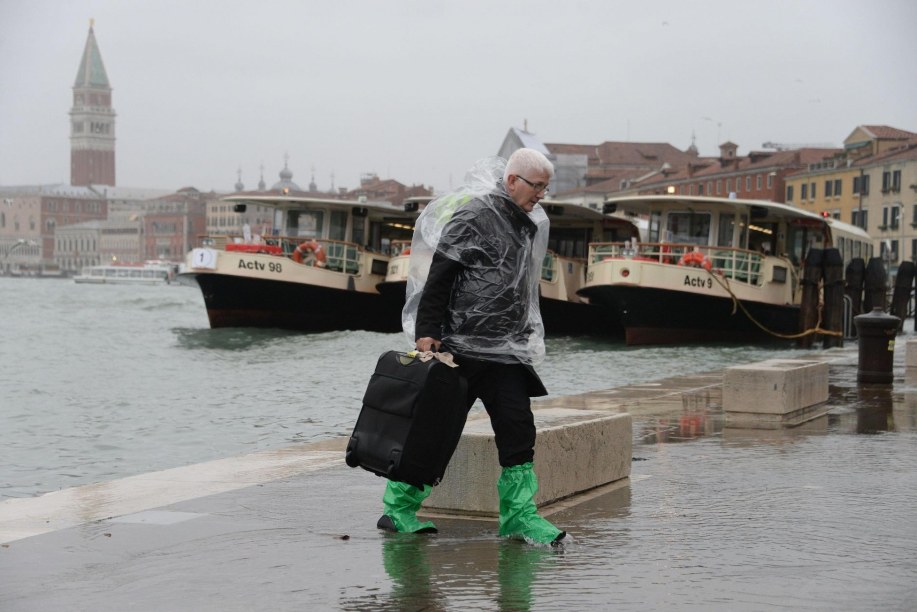 A man walks in a flooded street of Venice, Italy, backdropped by St. Marks Basilica bell tower, Monday, Oct. 29, 2018, as, according to city officials, 70 percent of the lagoon city has been flooded by waters rising 149 centimeters (more than 58 1/2 inches) above sea level. Venice frequently floods when high winds push in water from the lagoon, but Monday's levels are exceptional and forecast to rise even higher, to 160 centimeters (nearly 63 inches) by mid-afternoon. (Andrea Merola/ANSA via AP)