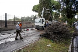 """Workers cut up and remove a fallen tree a day after strong winds and rain hit the city, in Rome, Tuesday, Oct. 30, 2018. The national Civil Protection Agency has issued red and orange alerts -- meaning possible """"loss of life"""" from landslides, floods, and infrastructural damage -- due to an Atlantic storm system that has brought torrential rains and hail, electrical storms, powerful winds and high seas to Italy from North to South. (AP Photo/Andrew Medichini)"""
