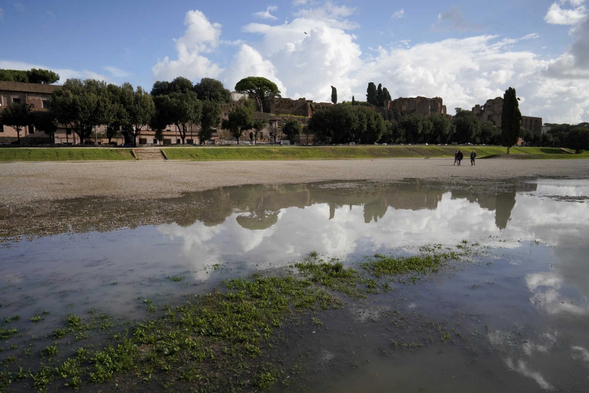"""People go for a walk in a partially flooded Circus Maximus a day after strong winds and rain hit the city, in Rome, Tuesday, Oct. 30, 2018. The national Civil Protection Agency has issued red and orange alerts -- meaning possible """"loss of life"""" from landslides, floods, and infrastructural damage -- due to an Atlantic storm system that has brought torrential rains and hail, electrical storms, powerful winds and high seas to Italy from North to South. (AP Photo/Andrew Medichini)"""