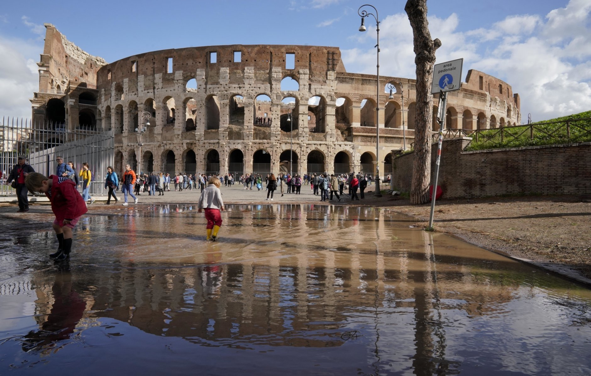 """Children play in a puddle by the ancient Colosseum a day after strong winds and rain hit the city, in Rome, Tuesday, Oct. 30, 2018. The national Civil Protection Agency has issued red and orange alerts -- meaning possible """"loss of life"""" from landslides, floods, and infrastructural damage -- due to an Atlantic storm system that has brought torrential rains and hail, electrical storms, powerful winds and high seas to Italy from North to South. (AP Photo/Andrew Medichini)"""