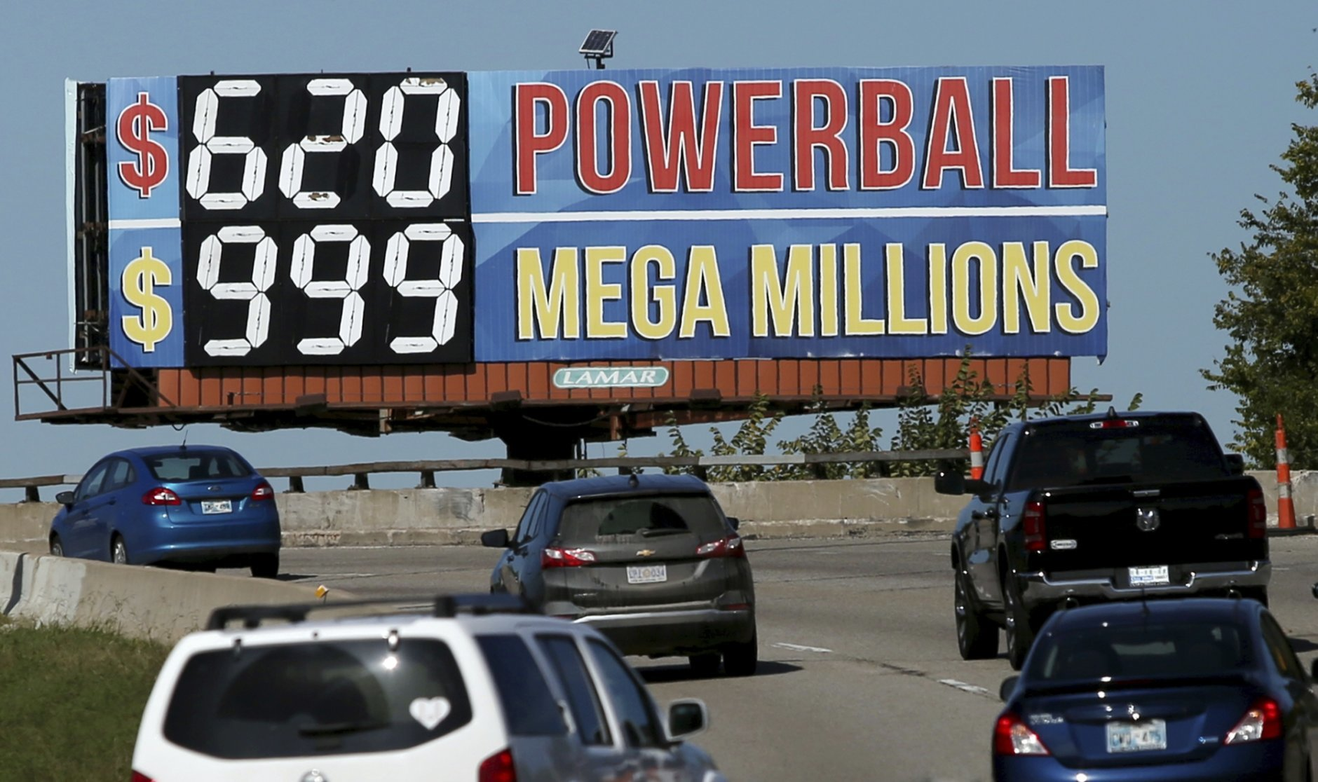 In this Monday, Oct. 22, 2018 photo, drivers on the Broken Arrow Expressway pass a sign with the Powerball and Mega Millions jackpot numbers as they drive toward downtown Tulsa, Okla., Monday, October 22, 2018. (John Clanton/Tulsa World via AP)