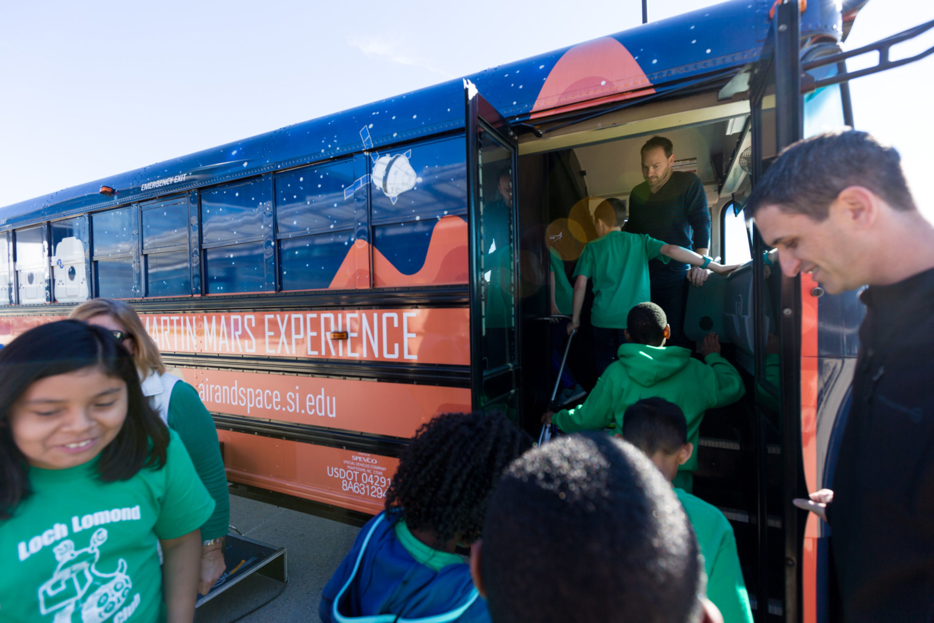 Students from the Manassas, Virginia's Loch Lomond Elementary School robotics team were the first ones to board the Lockheed Martin Mars Experience Bus after a morning ceremony at the Steven F. Udvar-Hazy Center in Chantilly, Virginia, Oct. 19, 2018. Lockheed Martin donated the bus, fitted with high-definition monitors on the windows, which provide visitors an opportunity to experience the Martian surface. (Air and Space Museum/Daniel Soñé)