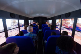 Students and chaperones from Virginia's Loch Lomond Elementary School robotics team watch as they seem to travel across the surface of the planet Mars, seated in the Lockheed Martin Mars Experience bus at the the Steven F. Udvar-Hazy Center, in Chantilly, Oct. 19, 2018. The bus, fitted with high-definition monitors on the windows, provides visitors an opportunity to experience the Martian surface. (Air and Space photo by Daniel Soñé)