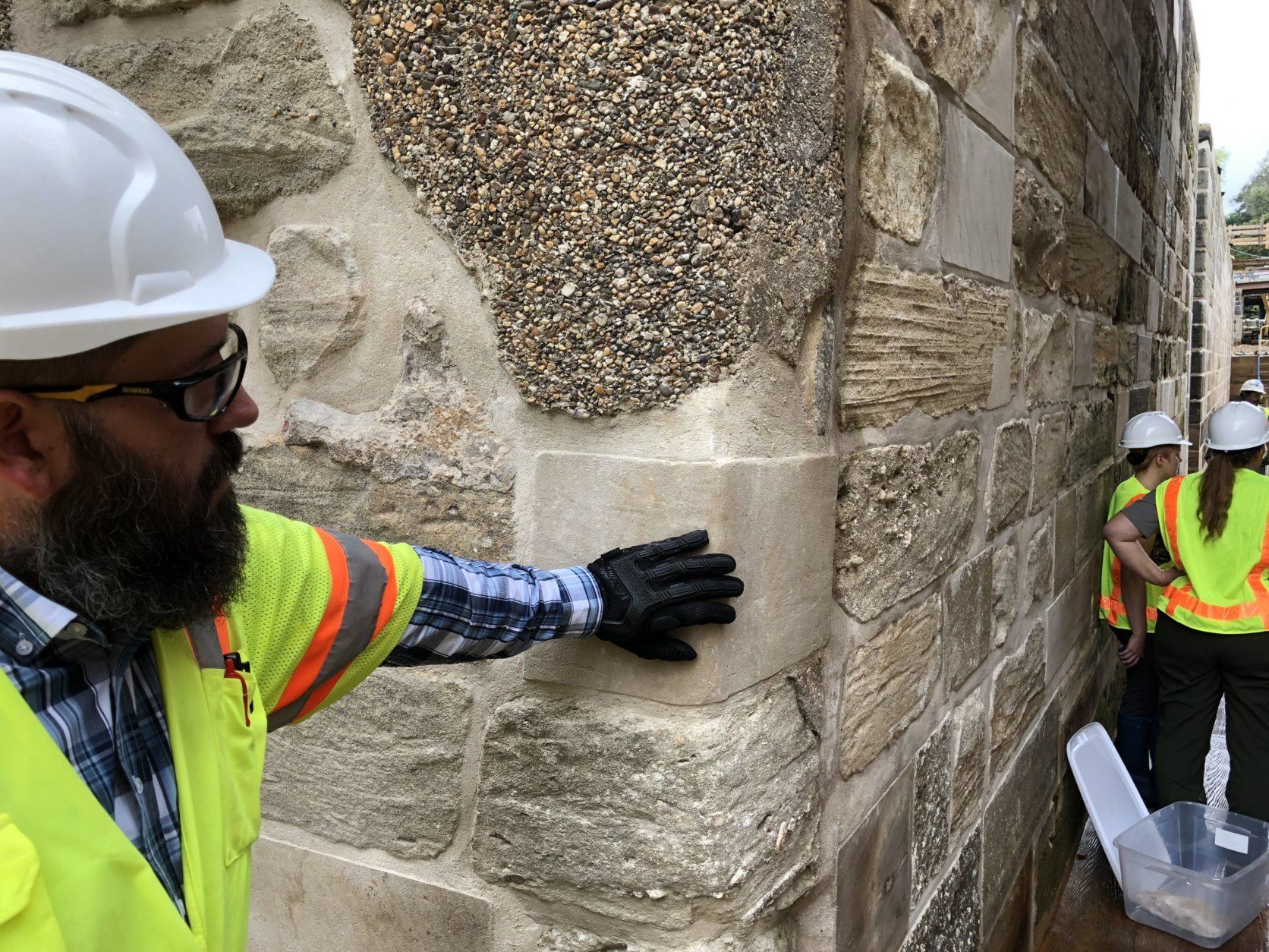 Construction manager Michael Lemaster takes a brief break while reporters are being briefed by park rangers. The dappled portion of the wall above his hand is an old concrete repair patch. He's touching a new stone that's part of the restoration project. Below Lemaster's hand is original stone from construction between the late 1820s and early 1830s. (WTOP/Kristi King)
