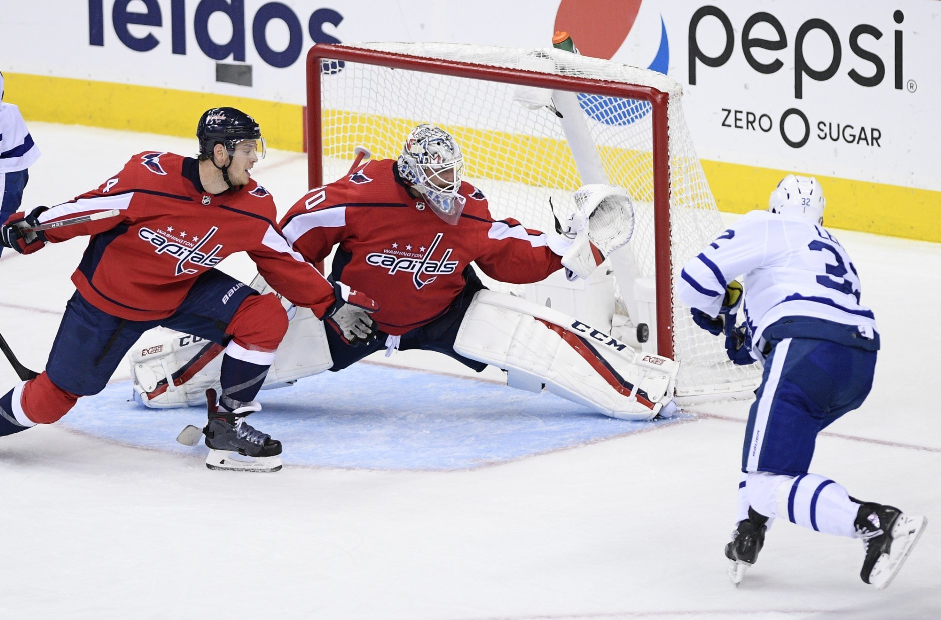 Toronto Maple Leafs left wing Josh Leivo (32) scores a goal past Washington Capitals goaltender Braden Holtby (70) and defenseman John Carlson, left, during the third period of an NHL hockey game, Saturday, Oct. 13, 2018, in Washington. The Maple Leafs won 4-2. (AP Photo/Nick Wass)
