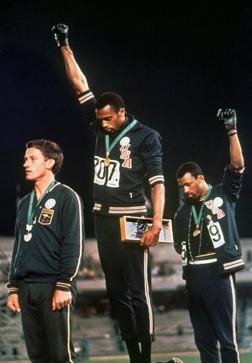 FILE - In this Oct. 16, 1968 file photo, extending gloved hands skyward in a Black power salute as a form of racial protest, U.S. athletes Tommie Smith, center, and John Carlos stare downward during the playing of national anthem after Smith received the gold and Carlos the bronze for the 200 meter run at the Summer Olympic Games in Mexico City. While the games were marked by dissent, today's situation in Mexico is much more chaotic with a government that is barely in control of many aspects of society, battered by violent drug cartels that are often supported by rogue cops and mayors. (AP Photo, File)