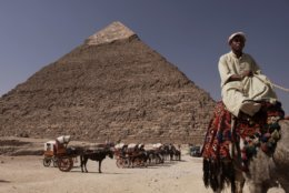 FILE - In this Oct. 11, 2012 file photo, an Egyptian camel owner waits for customers to take a ride, in front of the Khafre pyramid, near Cairo, Egypt. The Antiquities Ministry said in a statement Wednesday Oct. 31, 2018, that the second of Egypt's three famed pyramids of Giza will open to tourists this week after the completion of restoration work that lasted about two months. The pyramid of King Khafre, one of the three Great Pyramids gracing the Giza province south of Cairo, will be ready to receive tourists starting Thursday. (AP Photo/Nariman El-Mofty, File)