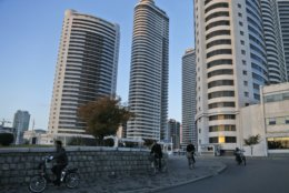 """In this Saturday, Oct. 27, 2018 photo, people ride their bikes past high rise buildings in downtown Pyongyang, North Korea. North Korea is exploring a grand plan to become a regional transportation hub, inspired in part by the successes of Singapore and Switzerland, and would be open to joining world financial institutions such as the International Monetary Fund if current member states give up their """"hostile"""" policies toward it, a senior government economist has told The Associated Press. (AP Photo/Dita Alangkara)"""