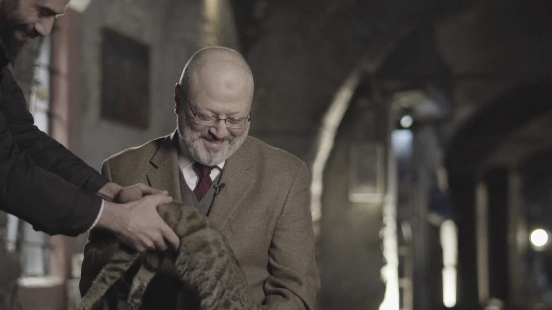 """In this image made from a March 2018 video provided by Metafora Production, Eiad Alhaji, a Syrian documentary film maker, grabs a cat that jumped onto Jamal Khashoggi's lap as he speaks in an interview at an undisclosed location. Eighteen days after Khashoggi disappeared, Saudi Arabia acknowledged early Saturday, Oct. 20, 2018, that the 59-year-old writer has died in what it said was a """"fistfight"""" inside the Saudi consulate in Istanbul. (Metafora Production via AP)"""