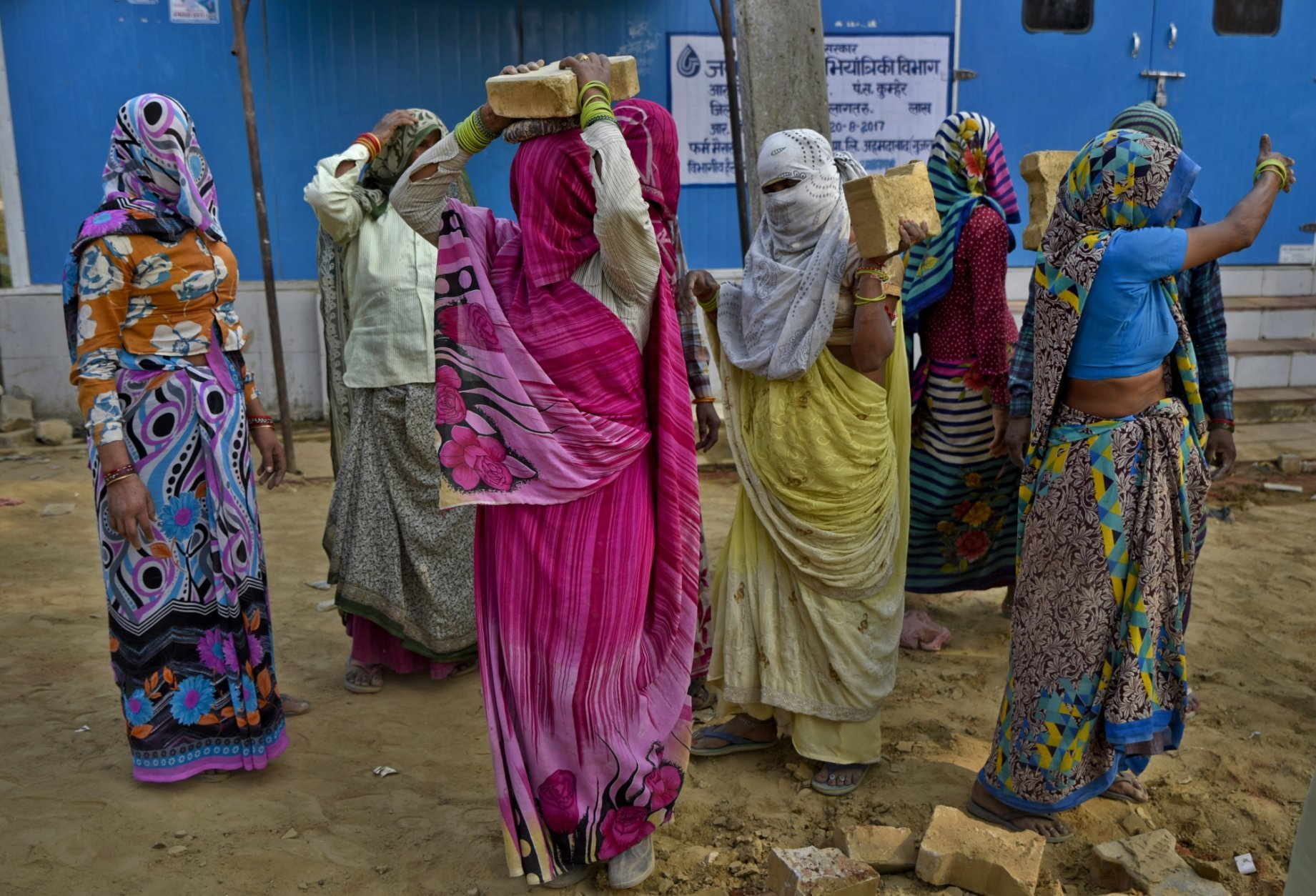 Rural women carry tiles that are being removed from a roadside at a village in Bharatpur, Rajasthan state, India, Saturday, Oct. 20, 2018. An Indian government scheme provides at least 100 days of guaranteed wage employment every year to every household whose adult members volunteer to do unskilled manual work. (AP Photo/R S Iyer)