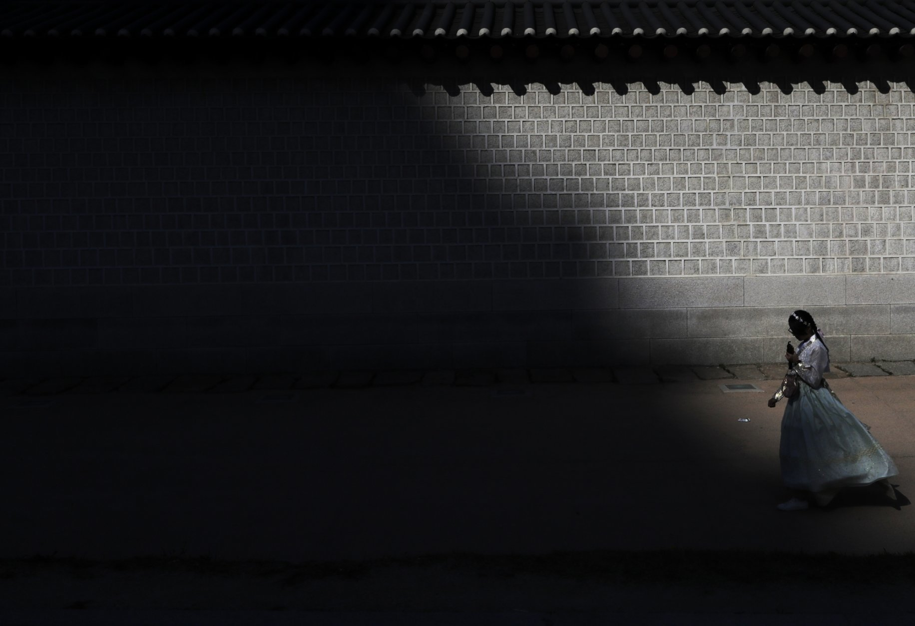 """A visitor dressed in traditional South Korean """"Hanbok"""" clothing walks along a wall outside the Gyeongbok Palace, the main royal palace during the Joseon Dynasty and one of South Korea's well known landmarks in Seoul, South Korea, Friday, Oct. 19, 2018. (AP Photo/Lee Jin-man)"""