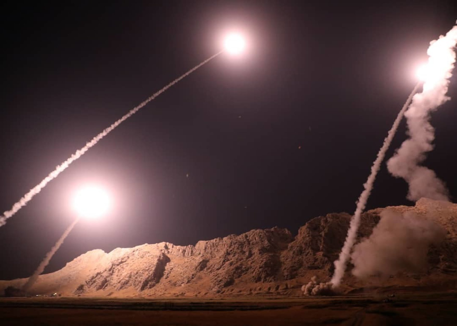 In this photo released by the Iranian Revolutionary Guard on Monday, Oct. 1, 2018, missiles are fired from the city of Kermanshah in western Iran targeting the Islamic State group in Syria. Iran's paramilitary Revolutionary Guard said Monday it launched ballistic missiles into eastern Syria targeting militants it blamed for a recent attack on a military parade. (Sepahnews via AP)