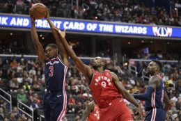 Washington Wizards guard Bradley Beal (3) grabs the rebound against Toronto Raptors forward Serge Ibaka (9) during the first half of an NBA basketball game, Saturday, Oct. 20, 2018, in Washington. Also seen is Wizards forward Jeff Green at right. (AP Photo/Nick Wass)