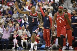 Washington Wizards guard Bradley Beal (3) gestures next to Toronto Raptors guard Lorenzo Brown (4) after he made a three-point basket during the first half of an NBA basketball game, Saturday, Oct. 20, 2018, in Washington. (AP Photo/Nick Wass)