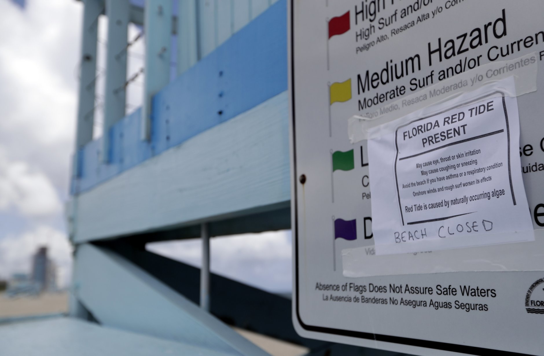 A sign posted on a lifeguard station warns of red tide at Haulover Beach Park, Thursday, Oct. 4, 2018, in Miami. Miami-Dade County closed beaches north of the Haulover inlet due to a rare outbreak of red tide along Florida's Atlantic Coast. Red tide is caused by algae and is common on Florida's Gulf Coast.  (AP Photo/Lynne Sladky)