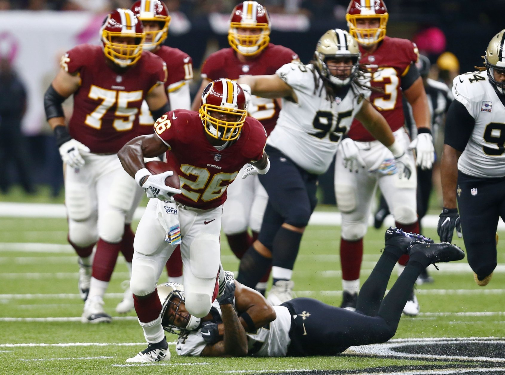 Washington Redskins running back Adrian Peterson (26) carries as New Orleans Saints strong safety Vonn Bell tries to tackle in the first half of an NFL football game in New Orleans, Monday, Oct. 8, 2018. (AP Photo/Butch Dill)