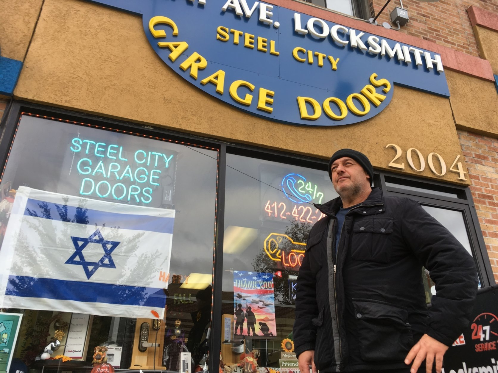 David Dvir stands in front of his business, Murray Avenue Locksmith, in the Squirrel Hill neighborhood of Pittsburgh, Monday, Oct. 29, 2018. Dvir, who was born in Israel but is an American citizen, voted for Donald Trump and doesn't agree with Jewish leaders who say the president shouldn't come to help mourn the victims of last week's synagogue massacre. (AP Photo/Allen G. Breed)