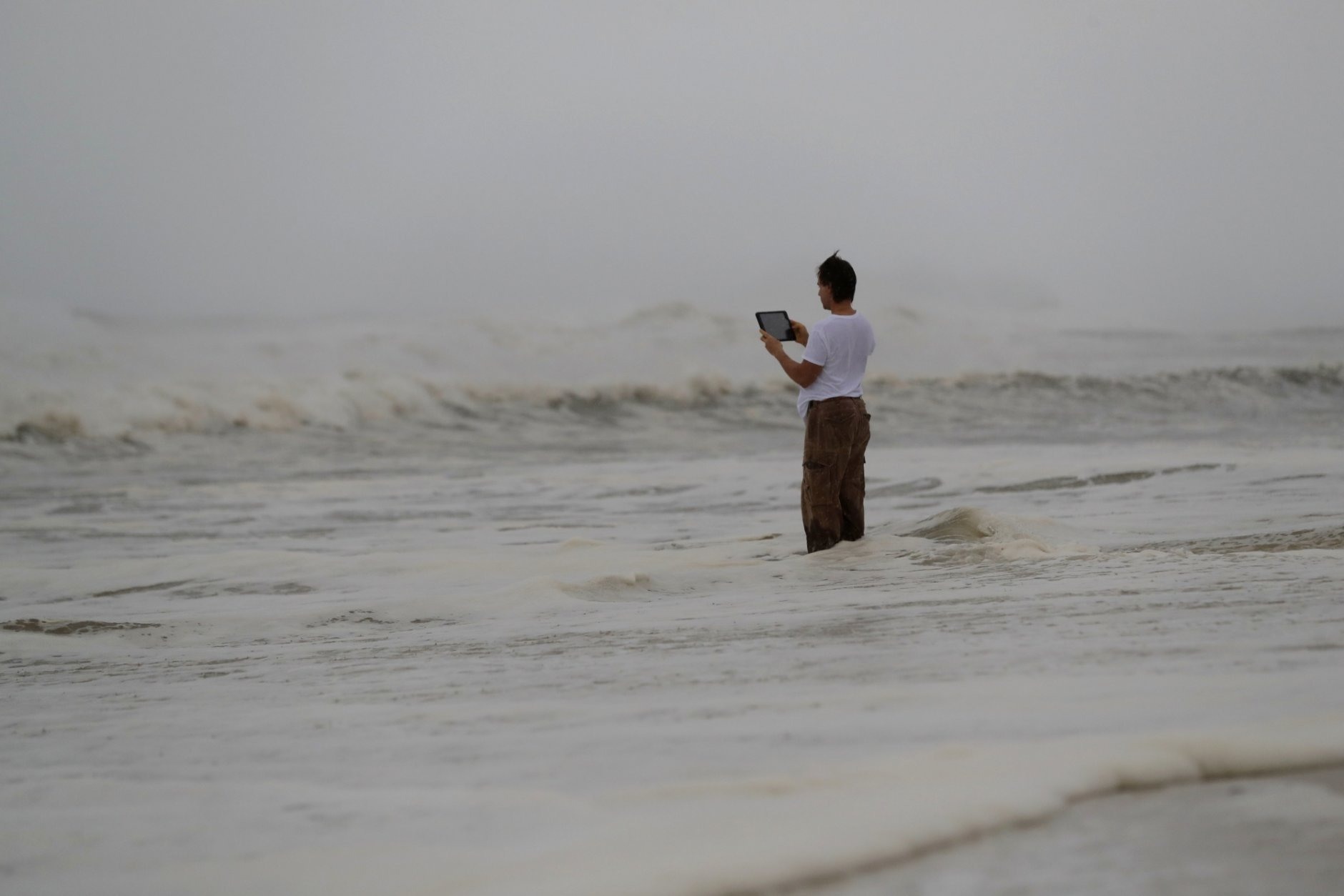 Peter Malave records the surf from encroaching Hurricane Michael, which is expected to make landfall today, in Panama City Beach, Fla., Wednesday, Oct. 10, 2018.  The hurricane center says Michael will be the first Category 4 hurricane to make landfall on the Florida Panhandle.  (AP Photo/Gerald Herbert)