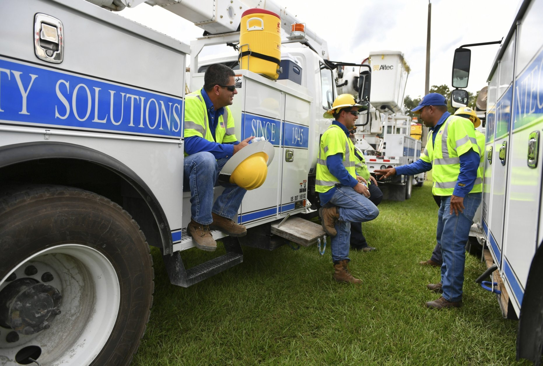 Pike Electric power restoration workers wait instructions after arriving at the Saraosta Fairgrounds on Tuesday, Oct. 9, 2018. Florida Power & Light is staging contractors in Sarasota, Fla, in advance of Hurricane Michael's expected landfall in the Florida panhandle later this week. (Mike Lang/Sarasota Herald-Tribune via AP)