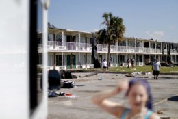 Residents come out out to a Red Cross food truck visiting the damaged motel where many continue to live despite the destruction in the aftermath of Hurricane Michael in Panama City, Fla., Tuesday, Oct. 16, 2018. (AP Photo/David Goldman)