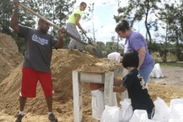 From left, Haskel Johnson, Daniel Tippett, Jennifer Tippett and Nobuko Johnson fill sand bags at the Lynn Haven Sports Complex in Lynn Haven, Fla., Monday, Oct. 8, 2018, to prepare for Hurricane Michael. (Patti Blake /News Herald via AP)
