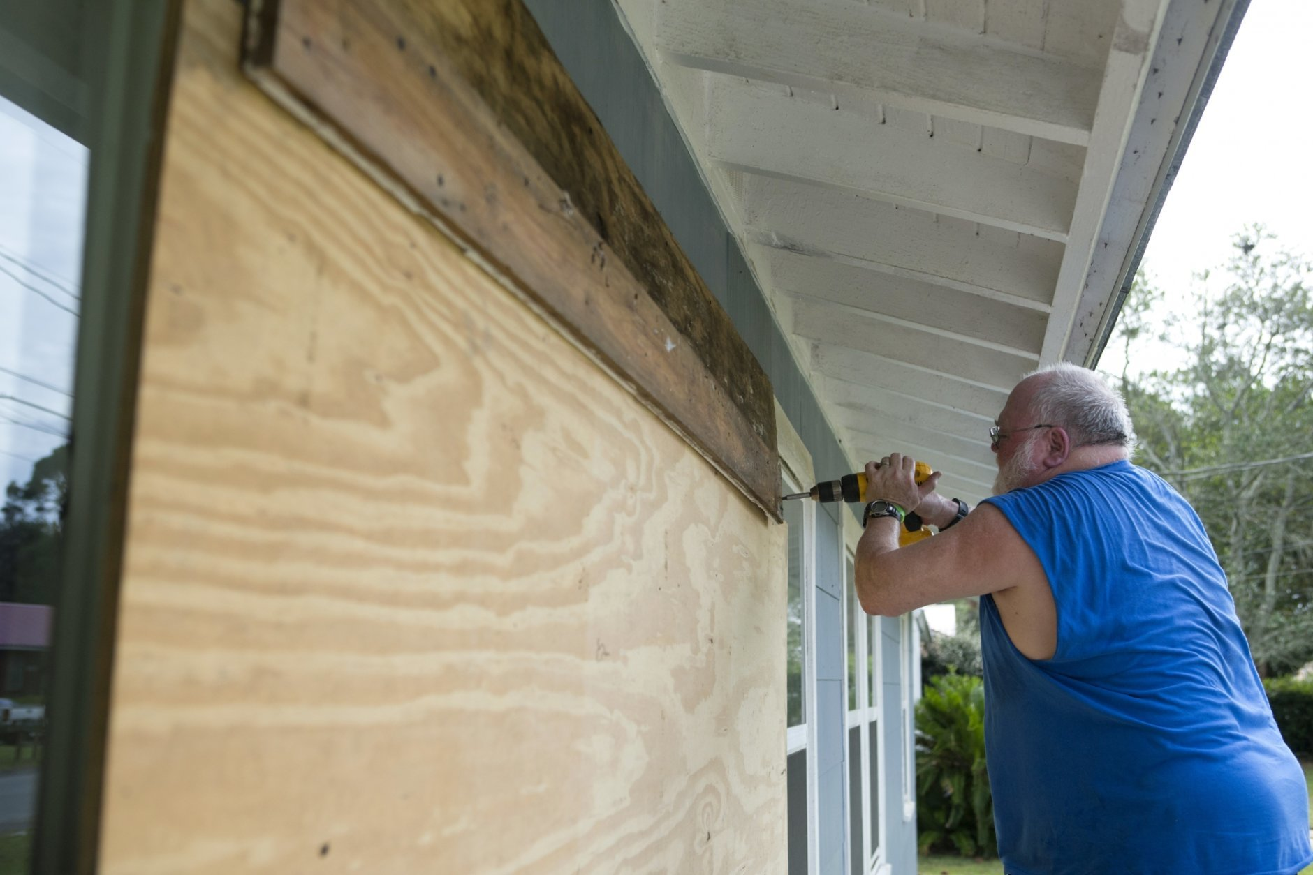 David Hayes boards up a window at this home in Panama City, Fla., as Hurricane Michael approaches on Tuesday, Oct. 9, 2018. (Joshua Boucher/News Herald via AP)