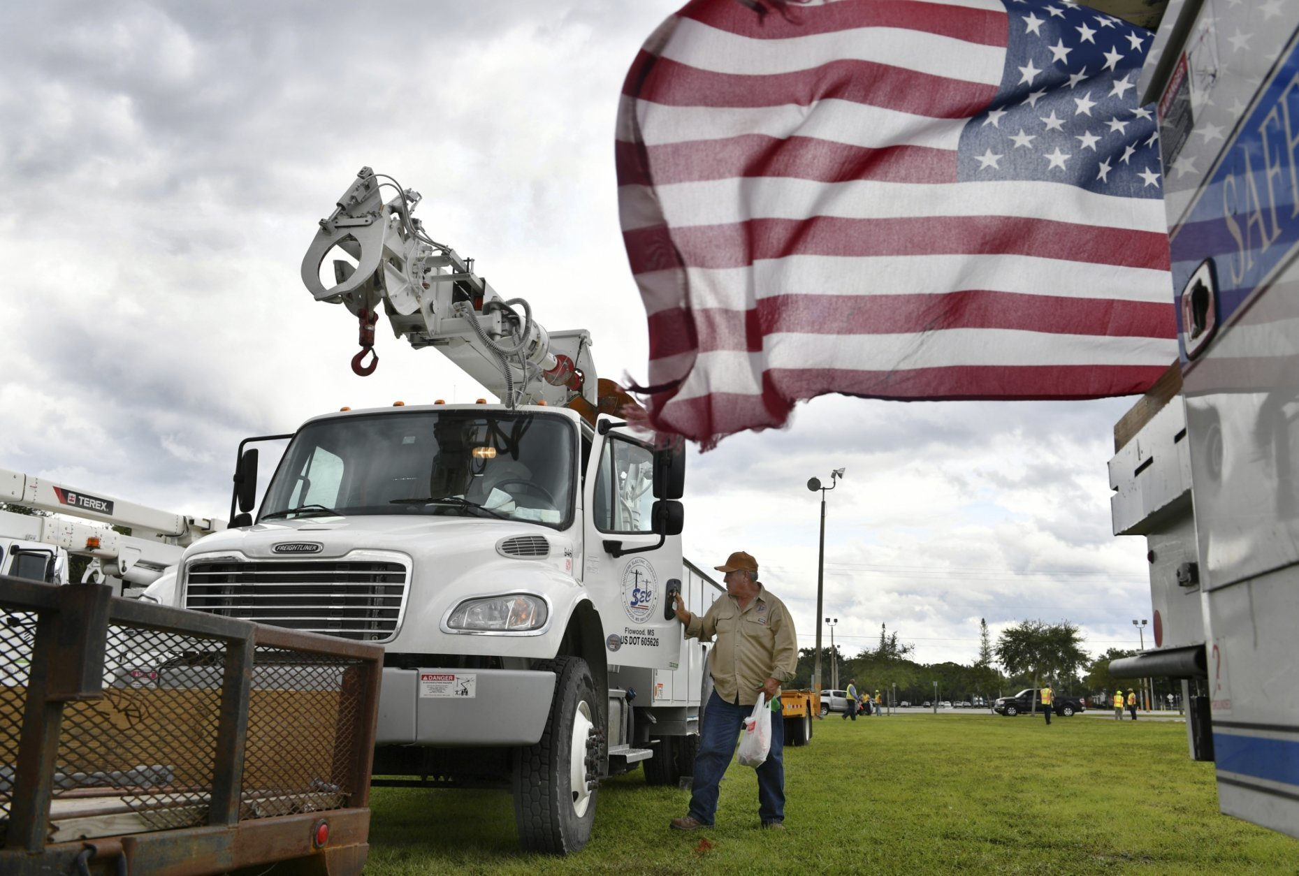 An employee of Southern Electric Corporation from Flowood, Miss., climbs out of the cab of his truck after arriving at the Sarasota Fairgrounds Tuesday, Oct. 9, 2018. Florida Power & Light is staging their power restoration contractors in Sarasota, Fla., in advance of Hurricane Michael's expected landfall in the Florida panhandle later this week. (Mike Lang/Sarasota Herald-Tribune via AP)