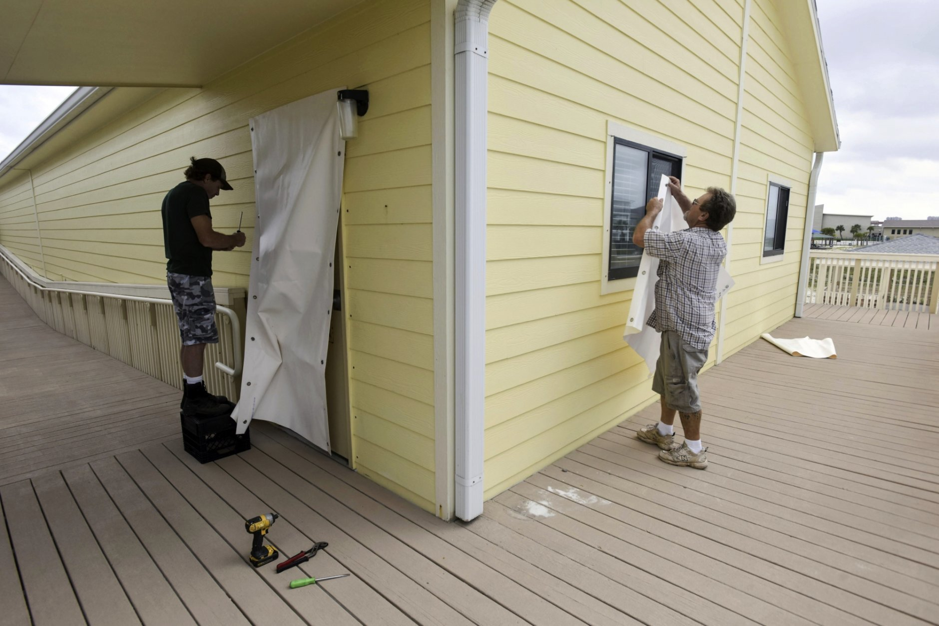 Volunteers install fabric storm panels at Pensacola Beach Elementary School, Tuesday, Oct. 9, 2018 in Pensacola, Fla. Hurricane Matthew is strengthening over the Gulf of Mexico and expected to make landfall in Florida's Panhandle or Big Bend area on Wednesday. Mandatory evacuations are in effect for coastal and low lying areas of the Florida Panhandle. ( Tony Giberson/Pensacola Beach News Journal via AP)/Palm Beach Post via AP)