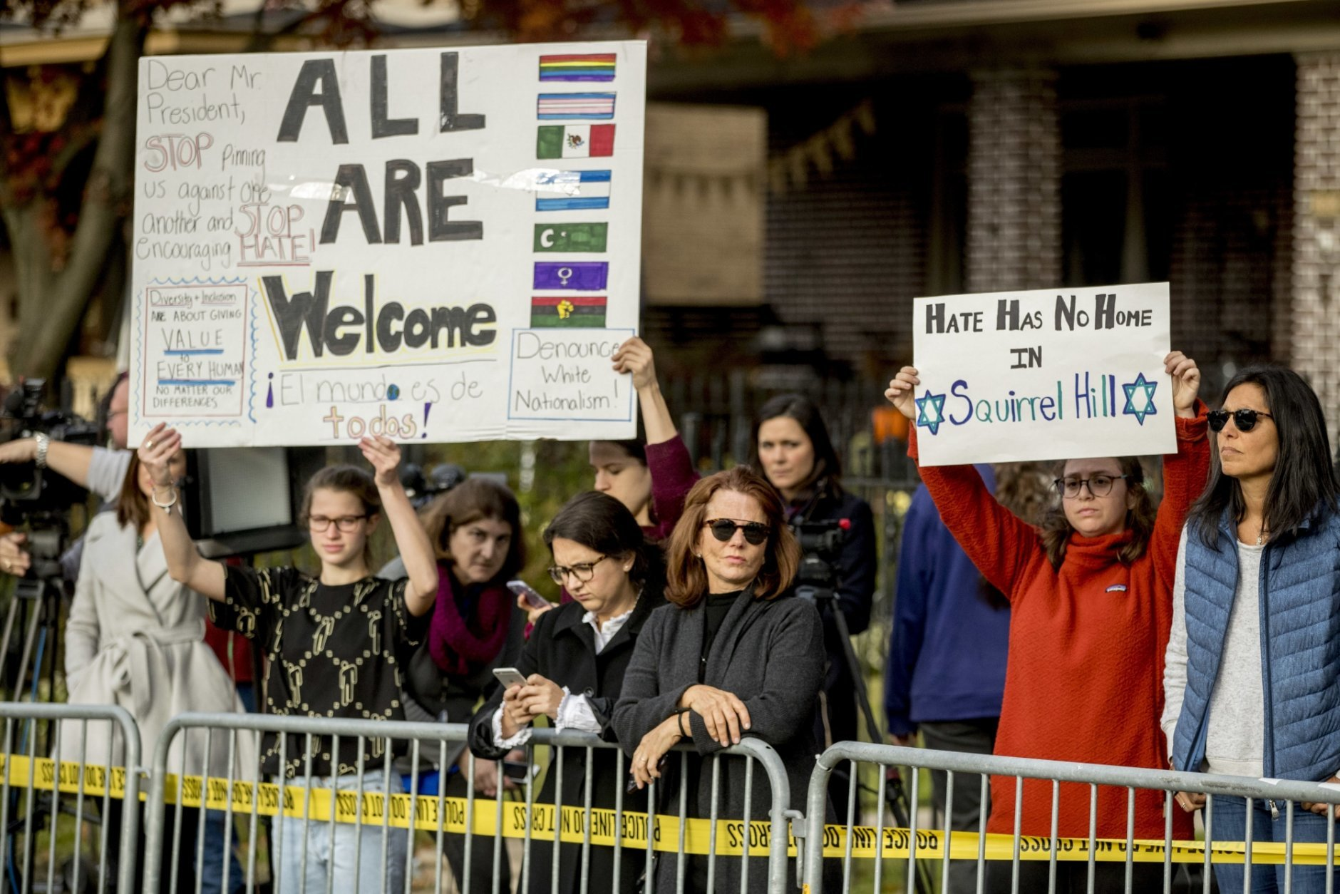 Members of the crowd hold up signs as President Donald Trump and first lady Melania Trump visit the Tree of Life Synagogue in Pittsburgh, Tuesday, Oct. 30, 2018. (AP Photo/Andrew Harnik)