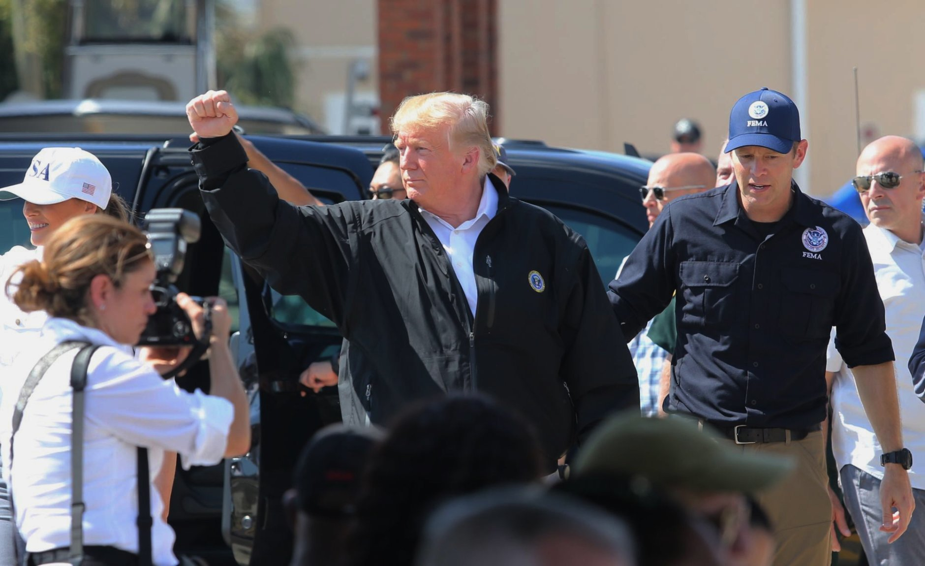 """President Donald Trump raises his fist to chants of """"USA"""" during a visit Monday, Oct. 15, 2018, to Lynn Haven, Fla., to see storm damage and recovery efforts following Hurricane Michael. Trump marveled at the roofless homes and uprooted trees he saw Monday while touring Florida Panhandle communities ravaged by the force of the hurricane. (Michael Snyder/Northwest Florida Daily News via AP)"""