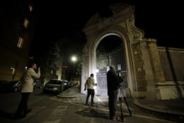 Reporters film the entrance of the Vatican embassy to Italy, Tuesday, Oct. 30, 2018. The Vatican said Tuesday that human bones were found during renovation work near the embassy, reviving speculation once again about one of the most enduring Vatican mysteries: the fate of Emanuela Orlandi, the 15-year-old daughter of a Vatican employee who disappeared in 1983. (AP Photo/Alessandra Tarantino)
