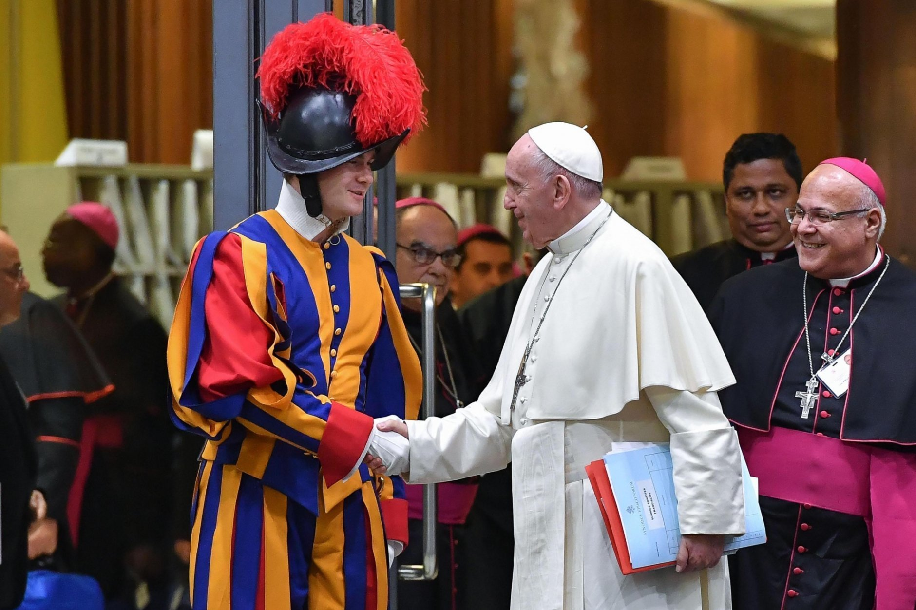 Pope Francis shakes hands with a Swiss Guard as he leaves after opening of the 15th Ordinary General Assembly of the Synod of Bishops, at the Vatican, Wednesday, Oct. 3, 2018. The Oct. 3-28 synod is opening under a fresh cloud of scandal with new revelations about decades of sexual misconduct and cover-up in the U.S., Chile, Germany and elsewhere. (Alessandro Di Meo/ANSA via AP)