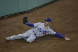 Los Angeles Dodgers' Cody Bellinger makes a sliding catch on a ball hit by Boston Red Sox's J.D. Martinez during the eighth inning of Game 2 of the World Series baseball game Wednesday, Oct. 24, 2018, in Boston. (AP Photo/Charles Krupa)