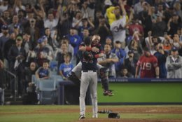 Boston Red Sox second baseman Dustin Pedroia jumps into Chris Sale's arms after Game 5 of baseball's World Series against the Los Angeles Dodgers on Sunday, Oct. 28, 2018, in Los Angeles. The Red Sox won 5-1 to win the series 4 game to 1. (AP Photo/Mark J. Terrill)