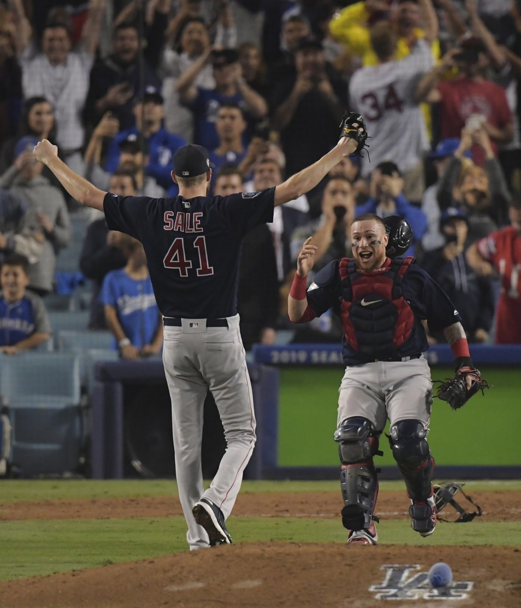 Boston Red Sox catcher Christian Vazquez celebrates Chris Sale's arms after Game 5 of baseball's World Series against the Los Angeles Dodgers on Sunday, Oct. 28, 2018, in Los Angeles. The Red Sox won 5-1 to win the series 4 game to 1. (AP Photo/Mark J. Terrill)