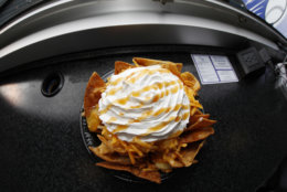 In this Saturday, May 6, 2017, a bowl of apple pie nachos is shown at Coors Field in Denver. The $6-bowl consists of cinnamon-covered nacho chips, apple pie filling, cheddar cheese, topped with whipped cream and then drizzled with caramel sauce. The concoction is rated at 740 calories. (AP Photo/David Zalubowski)
