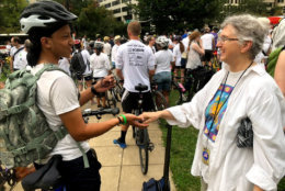 A large group of cyclists, mostly dressed in white, gathered at D.C.'s Farragut Square on Thursday to honor fallen fellow rider Thomas Hollowell. (WTOP/Mike Murillo)