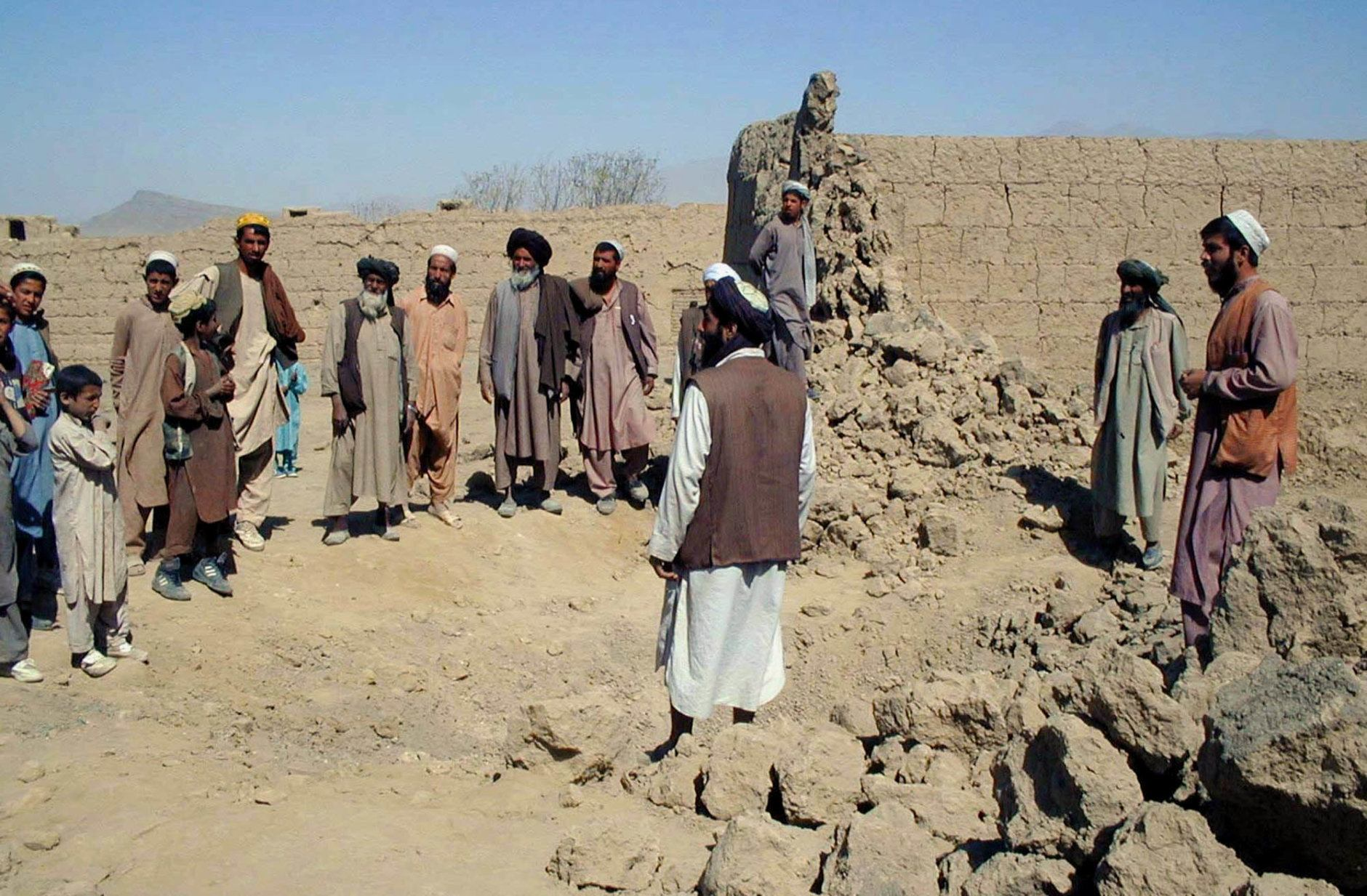 Residents look at the damage caused in a wall by a U.S. air strike in the village of Deh Sabz, 20 kilometers (13 miles) north of the Afghan capital Kabul Wednesday, Oct. 10, 2001. Warplanes pounded also  the Taliban's home base of Kandahar early Wednesday for the third time in 24 hours, targeting the airport outside the southern Afghan city (AP Photo/Amir Shah)