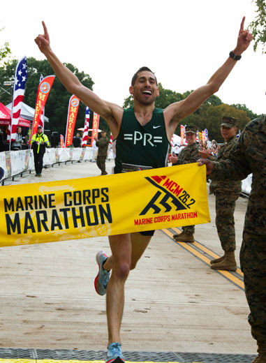 Jeffrey Stein rises his arms as he finish in the first place men's the 43rd Marine Corps Marathon, Sunday, Oct. 28, 2018, in Arlington, Va. (AP Photo/Jose Luis Magana)