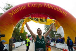 Jeffery Stein holds the banner as he crosses the finish line to win the Marine Corps Marathon men's division. (AP Photo/Jose Luis Magana)