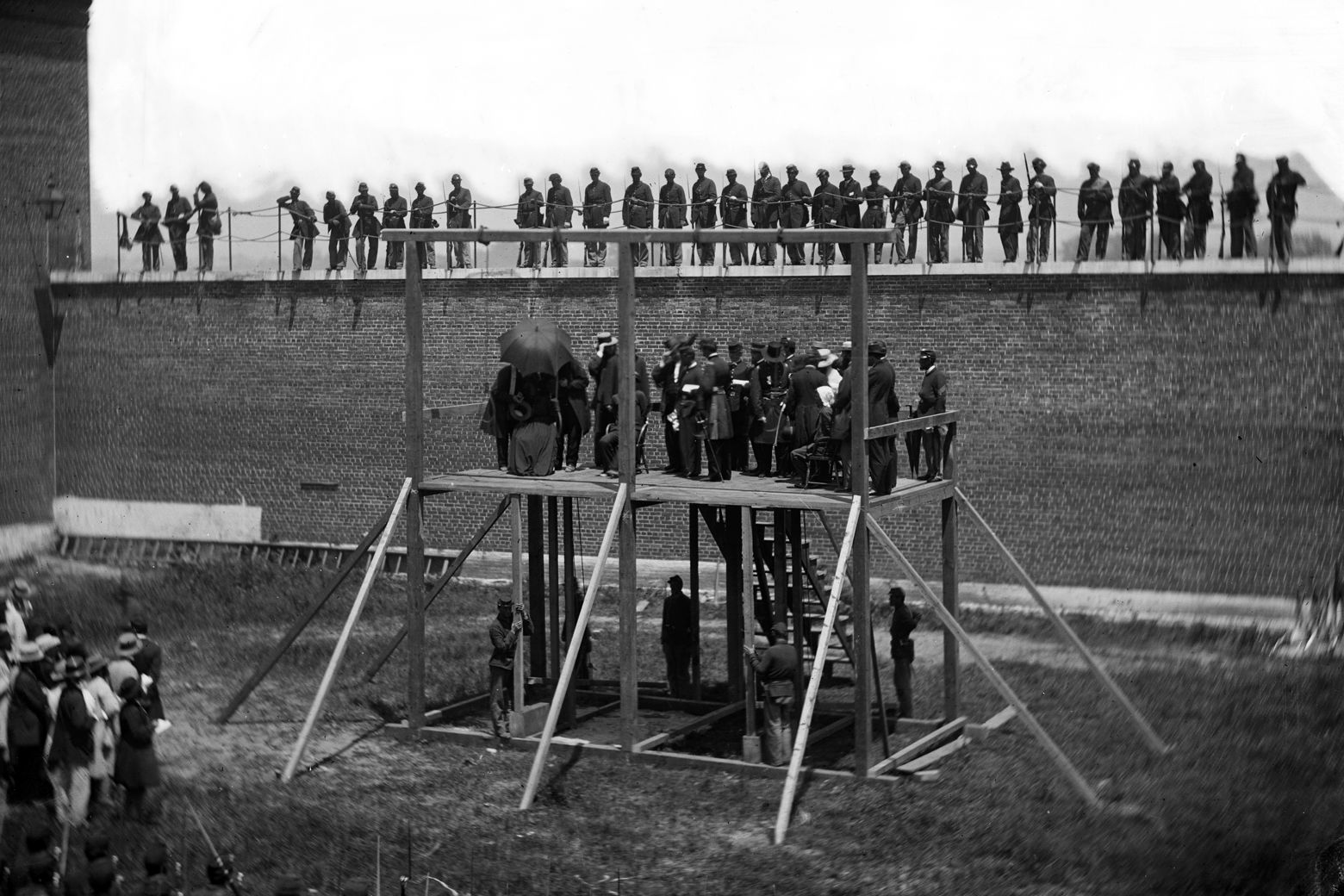 The four condemned Lincoln assassination conspirators (Mary Surratt, Lewis Payne, David E. Herold, George A. Atzerodt), with officers and others on the scaffold, with guards on the wall, in 1865. (Courtesy Library of Congress)