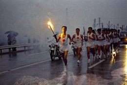 Japanese torchbearers of the Olympic flame relay team run through the rain on their way to the Olympic Stadium in October 1964 in Tokyo, Japan. The Olympic Flame is going to be lit by Yoshinori Sakai who was born in Hiroshima on August 6, 1945, the day the nuclear weapon destroyed that city. He symbolizes the rebirth of Japan after the Second World War when he opens the Summer Olympic Games on October 10, 1964 in Tokyo, Japan. (AP Photo)