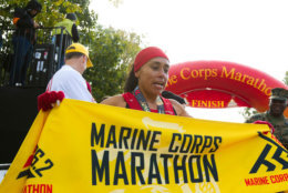 Jenny Mendez of Costa Rica holds the marathon banner after she finished in first place in the women's division of the 43rd Marine Corps Marathon, Sunday, Oct. 28, 2018, in Arlington, Va. (AP Photo/Jose Luis Magana)