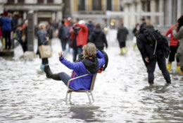 A woman sits as tourists make their way through flooded St. Mark's Square in Venice, Italy, Thursday, Nov. 1, 2018 as rainstorms and strong winds have been battering the country. Two people were killed when a falling tree crushed their car in the mountainous countryside in northwestern Italy, as rainstorms and strong winds continued to pummel much of the country. (AP Photo/Luca Bruno)