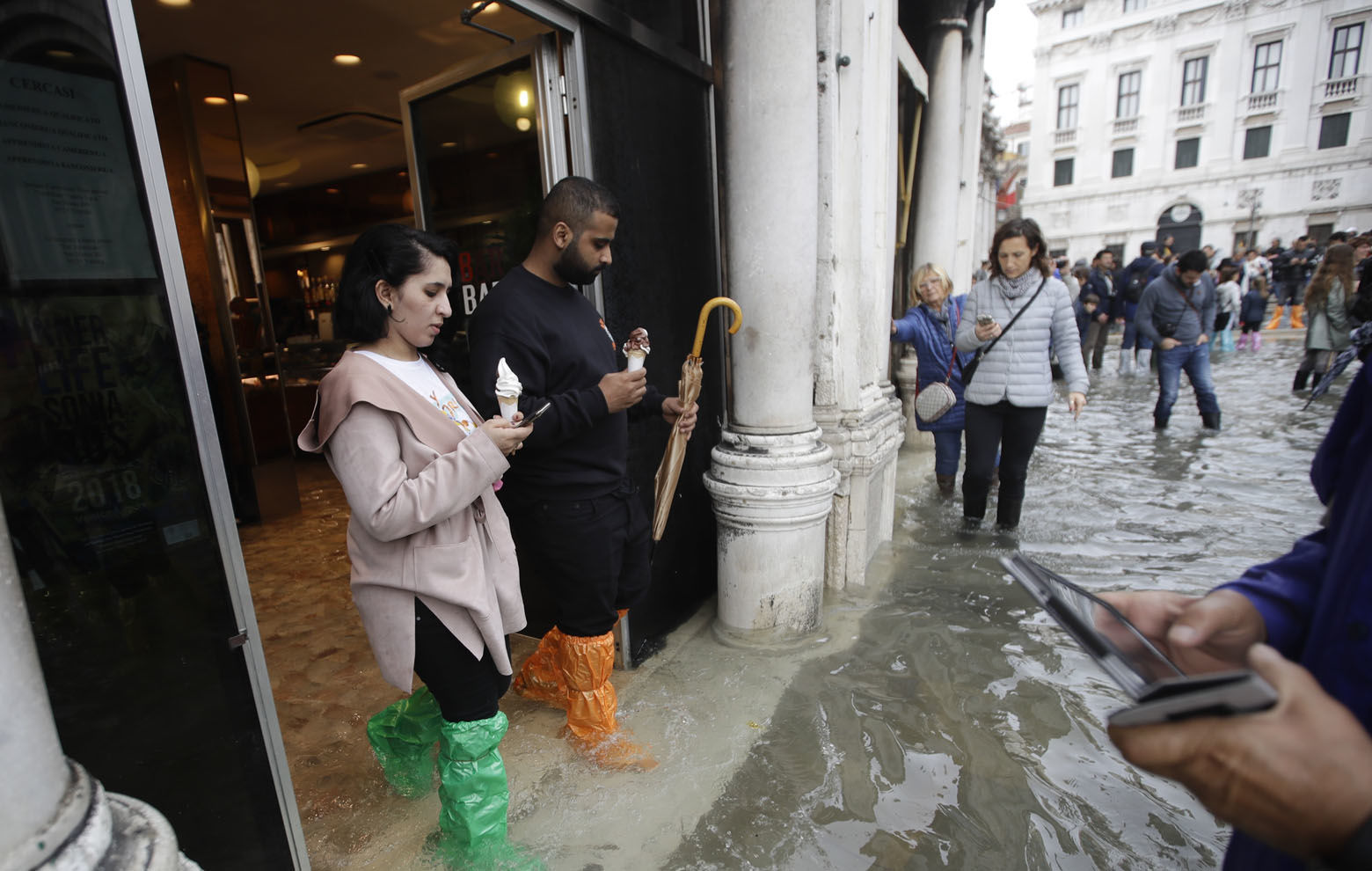Tourists check their smartphones in flooded St. Mark's Square in Venice, Italy, Thursday, Nov. 1, 2018 as rainstorms and strong winds have been battering the country. Two people were killed when a falling tree crushed their car in the mountainous countryside in northwestern Italy, as rainstorms and strong winds continued to pummel much of the country. (AP Photo/Luca Bruno)