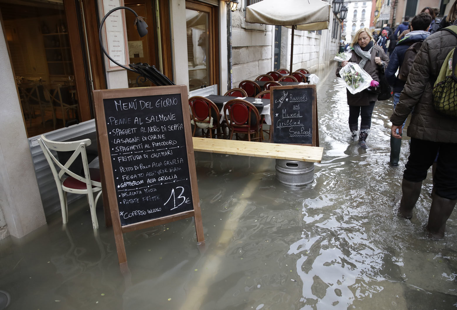 People walk next to a blackboard featuring a restaurant menu in flooded St. Mark's Square in Venice, Italy, Thursday, Nov. 1, 2018 as rainstorms and strong winds have been battering the country. Two people were killed when a falling tree crushed their car in the mountainous countryside in northwestern Italy, as rainstorms and strong winds continued to pummel much of the country. (AP Photo/Luca Bruno)