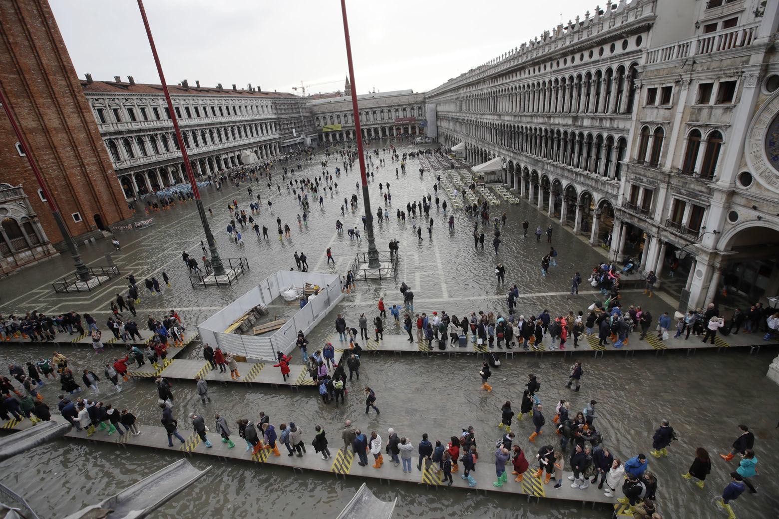 Tourists cross flooded St. Mark's Square in Venice, Italy, Thursday, Nov. 1, 2018 as rainstorms and strong winds have been battering the country. Two people were killed when a falling tree crushed their car in the mountainous countryside in northwestern Italy, as rainstorms and strong winds continued to pummel much of the country. (AP Photo/Luca Bruno)