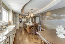 The kitchen includes sinks, two dishwashers and two islands, and a hand-painted mural of the sea. (Courtesy HomeVisit)