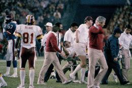 Washington Redskins quarterback Joe Theismann gestures as he is carried off the field at RFK Stadium in Washington, D.C., Nov. 18, 1985. Theismann injured his right leg during second quarter action. (AP Photo/J. Scott Applewhite)