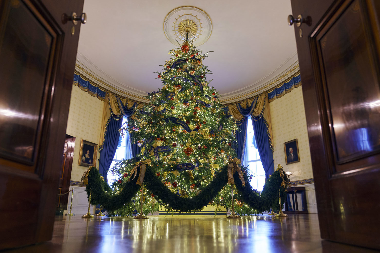 "The official White House Christmas tree is seen in the Blue Room during the 2018 Christmas Press Preview at the White House in Washington, Monday, Nov. 26, 2018. The tree measures 18 feet tall and is dressed in over 500 feet of blue velvet ribbon embroidered in gold with each State and territory. Christmas has arrived at the White House. First lady Melania Trump unveiled the 2018 White House holiday decor on Monday. She designed the decor, which features a theme of ""American Treasures."" (AP Photo/Carolyn Kaster)"